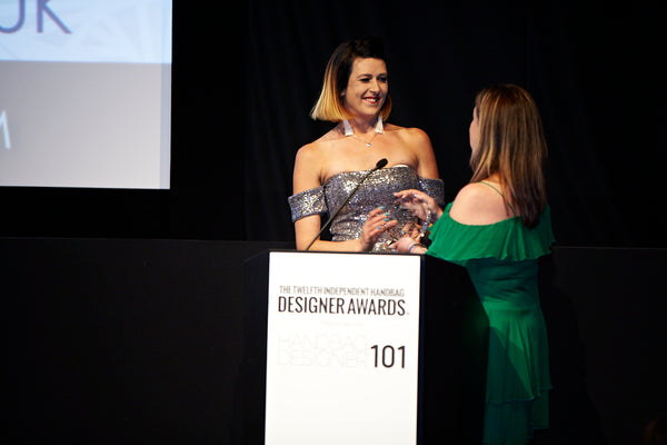 Jennifer Hamley recieves handbag designer award from Hallie Lorber of Taja Coconut