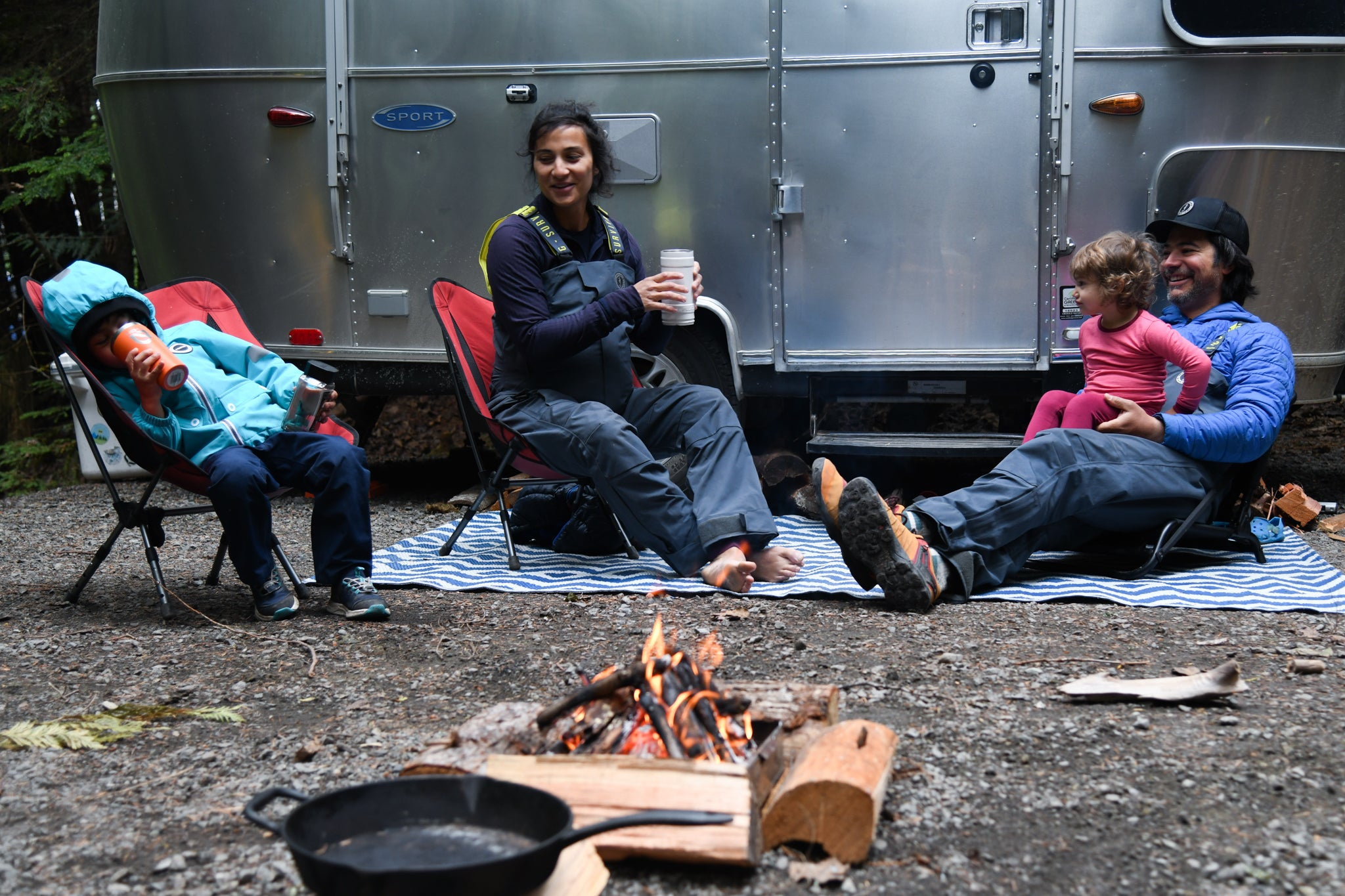 Family of four lounging by a campfire in front of a metal airstream trailer.