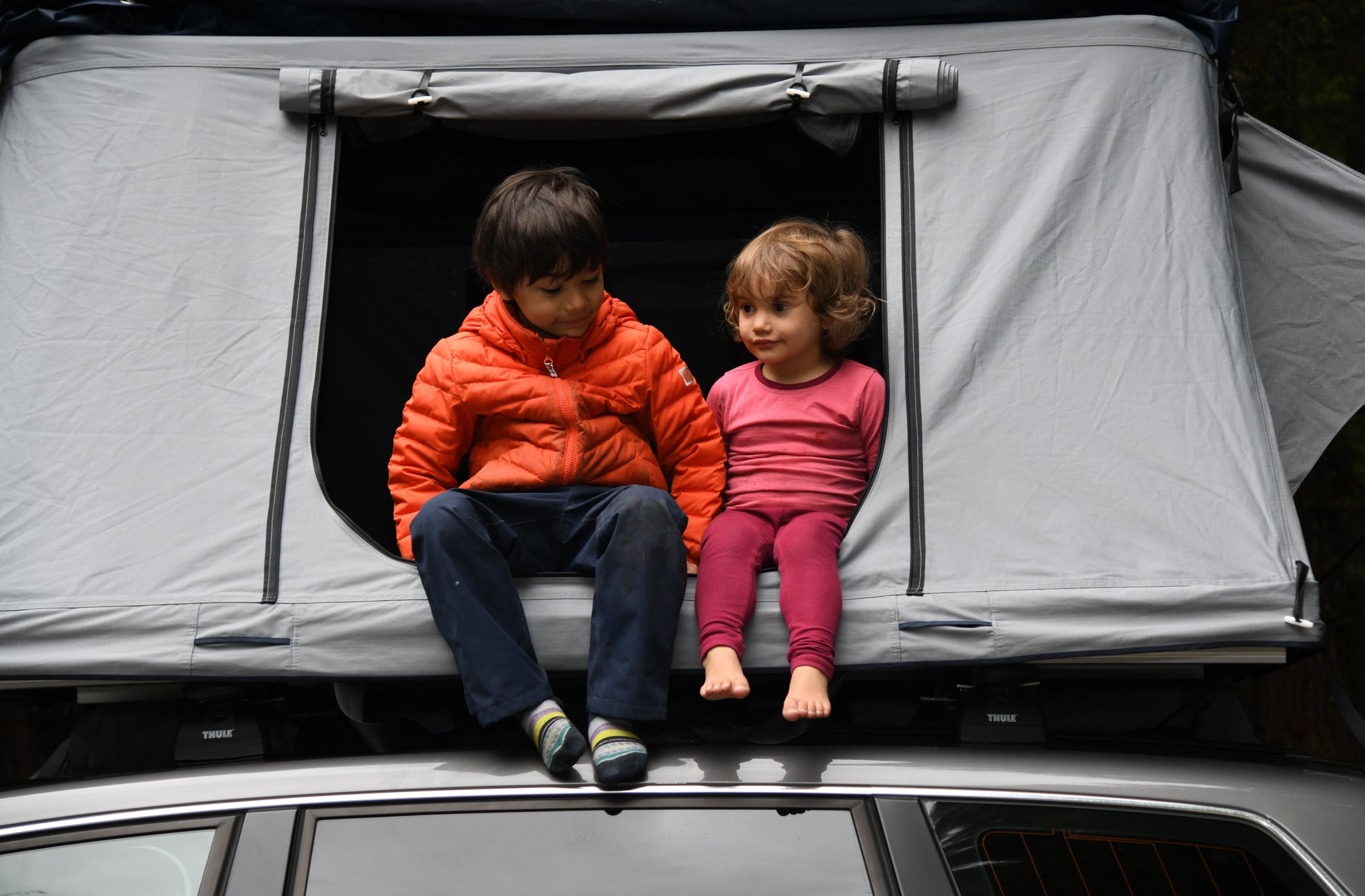 A young boy and girl sit in a roof top tent on a camping trip