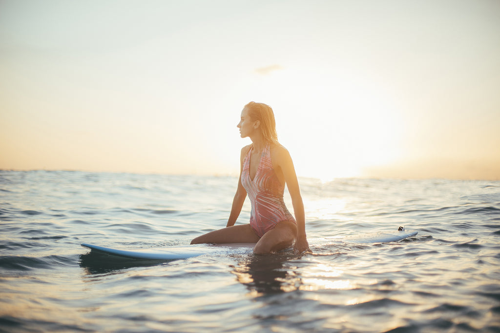 Woman on sitting on surfboard