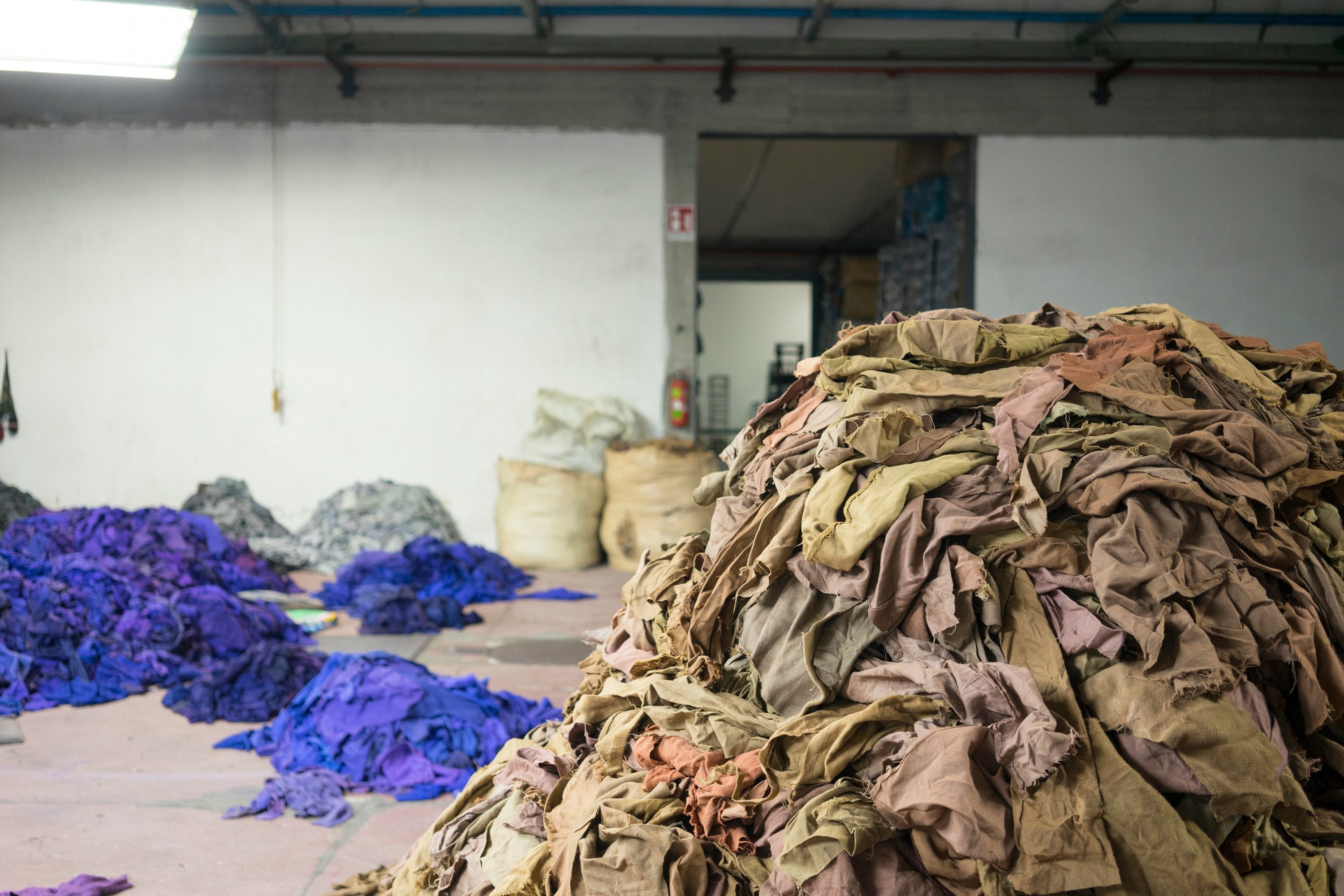 Used woollen garments shredded and sorted into colour piles, ready for recycling