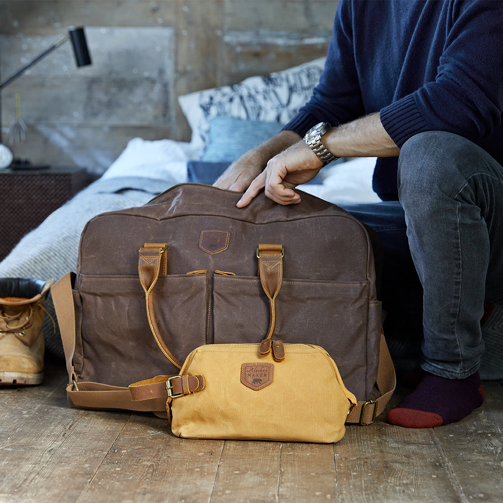 brown waxed canvas weekend bag with mustard toiletry bag