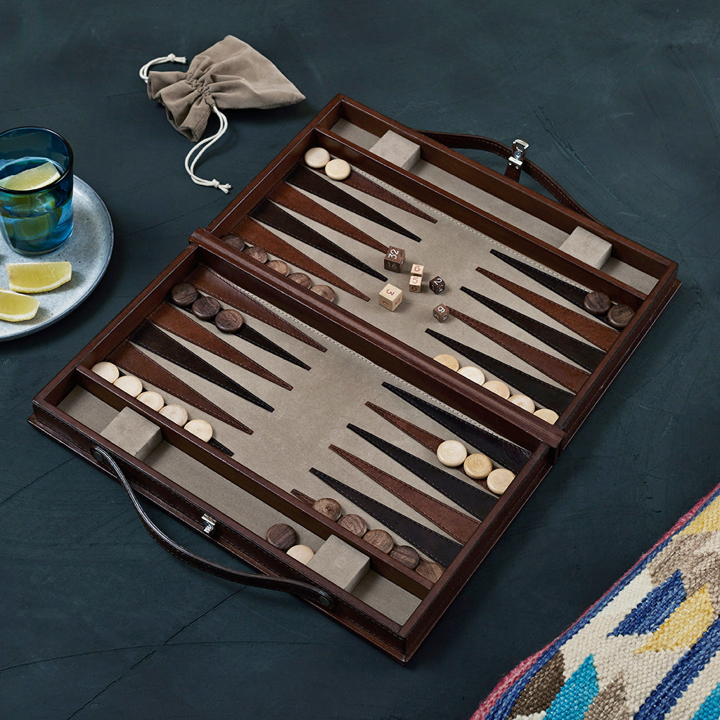 leather backgammon board open showing drawstring bag for pieces