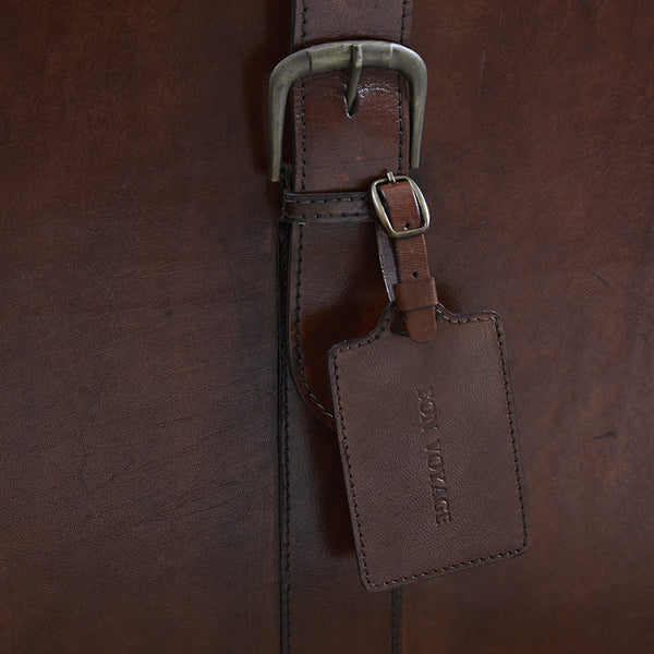 Leather luggage tag personalised and hangs off trunk