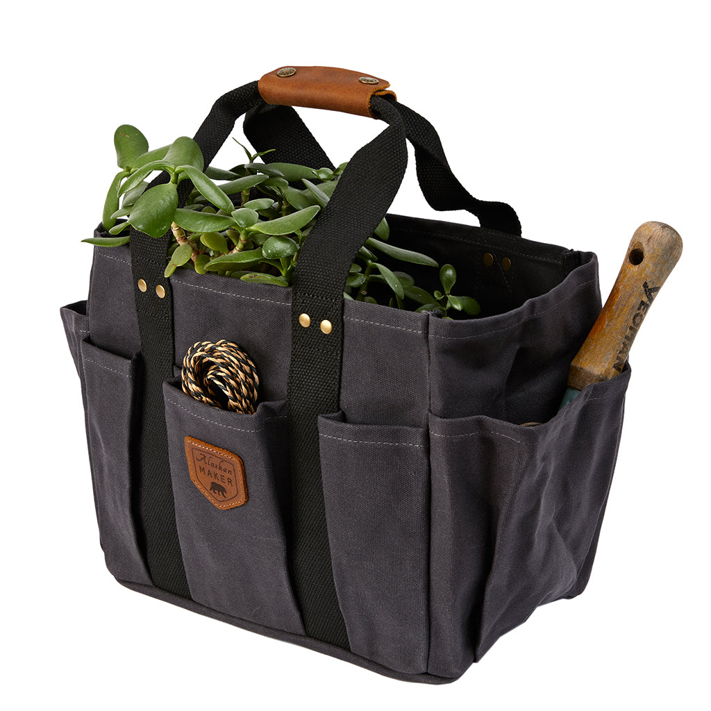 gardening bag filled with string, tools and a plant