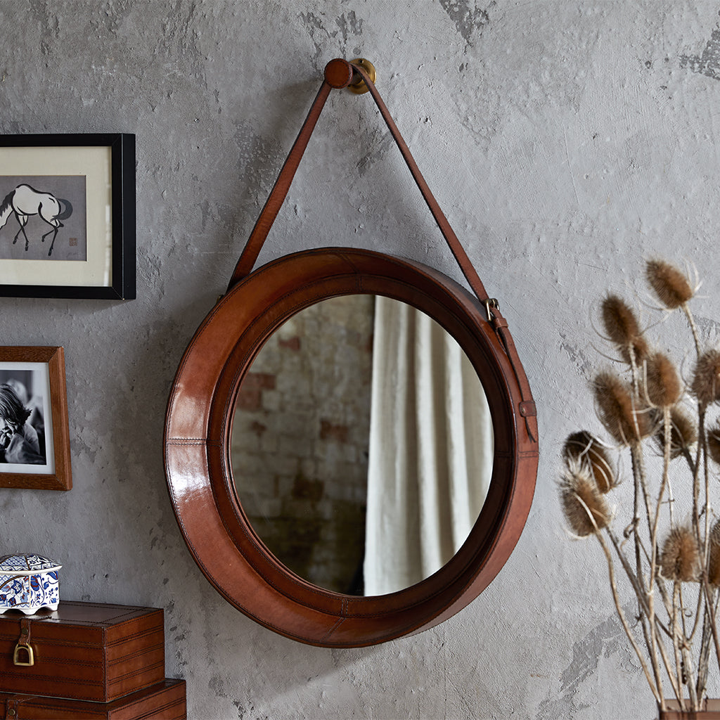 Leather rimmed mirror with leather strap