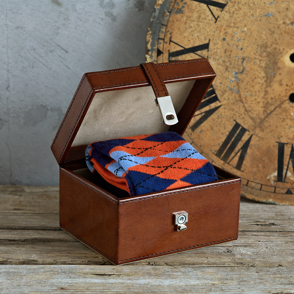 socks in a leather box orange argyle