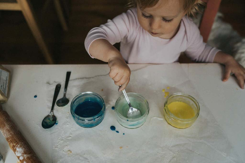 A child choosing between bowls of icing