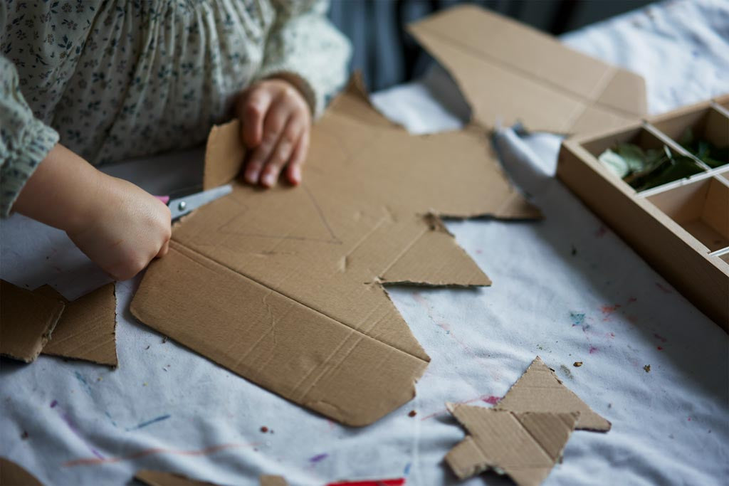 A child cutting Christmas tree decorations out of cardboard