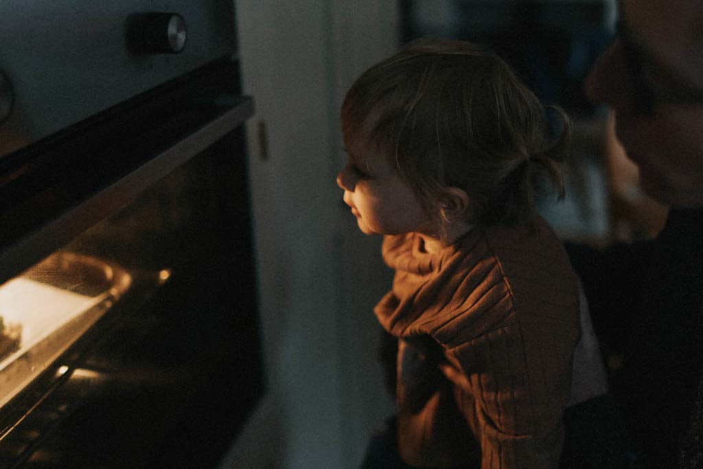 Child watching food in the oven