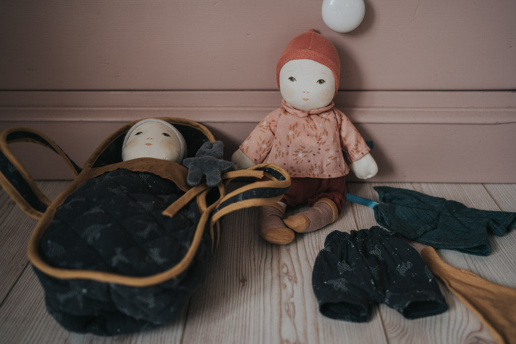 Moulin Roty's doll's beside each other, one in a carry cot