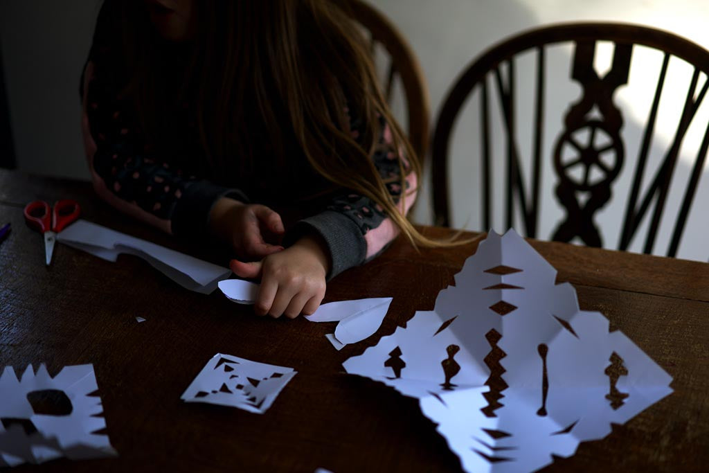 A child cutting a paper snowflake