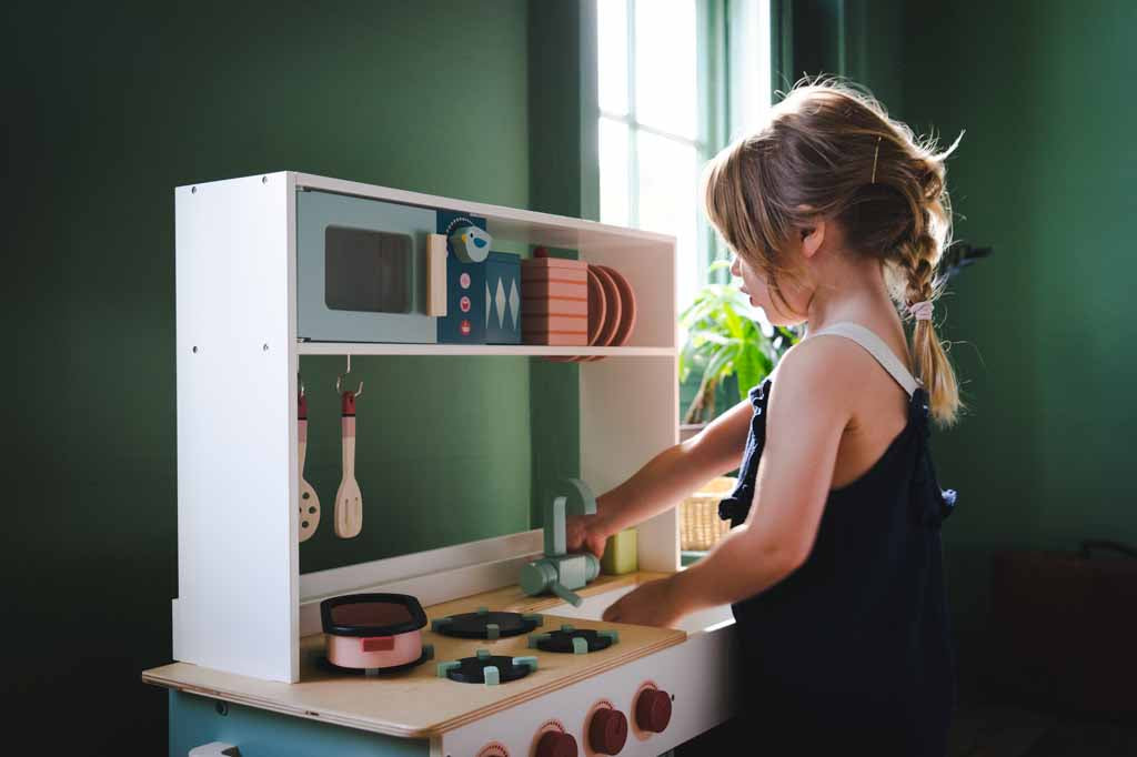 Girl playing with a play kitchen