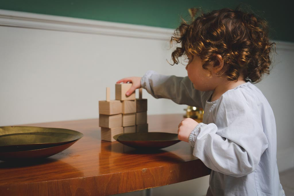 A toddler building a tower of blocks and learning to overcome challenges