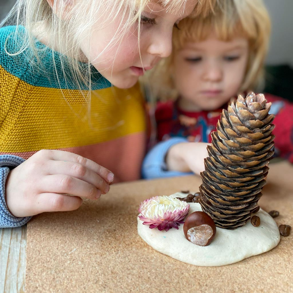 Pine cones and other loose-part natural materials stuck into playdough