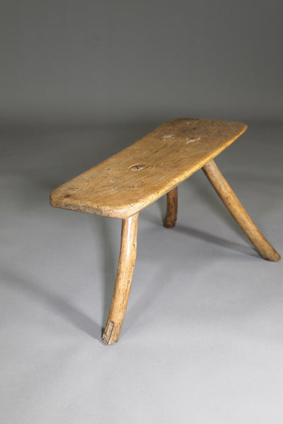 A fine example of a primitive early 19th c three legged sycamore stool