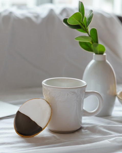 black and white biscuit leaning on white mug with plant behind it