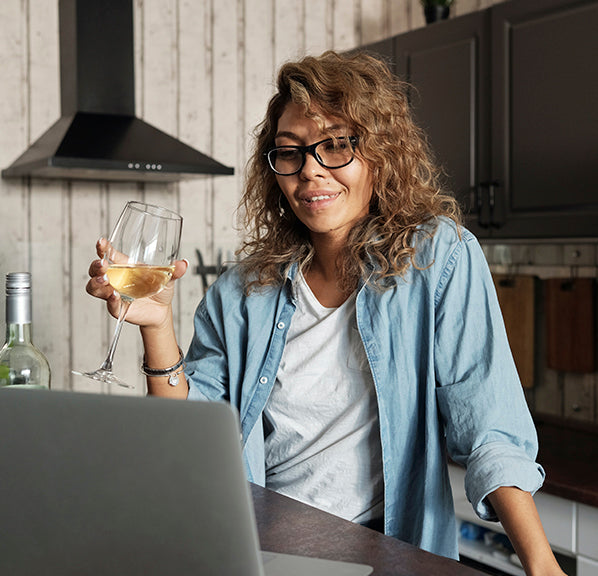 woman on video call in the kitchen drinking wine
