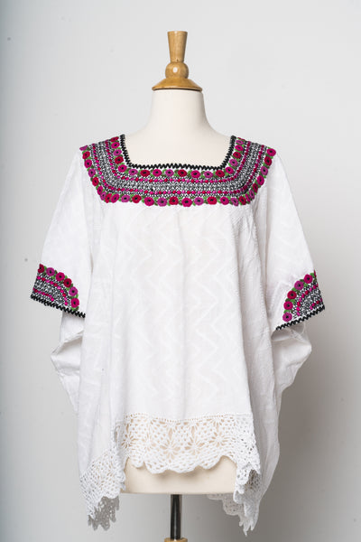 hand embroidered Guatemalan blouse with deep pink and green embroidery at neck and sleeves. Detailed bottom edge. perfect with jeans or as a cover-up. Fair trade, made by women. Chic global apparel by Larkin Lane