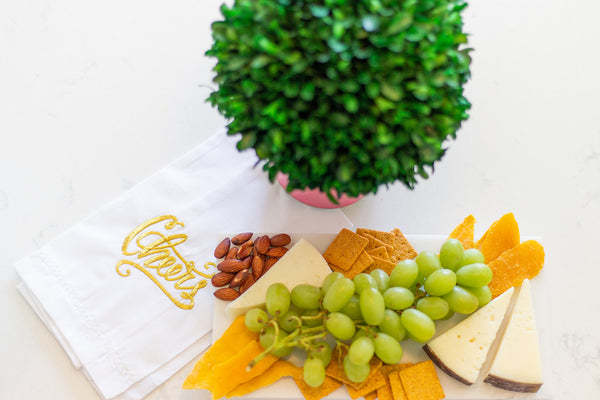 Marble cheese board with bar towel ready to serve guests- memorable hostess tip