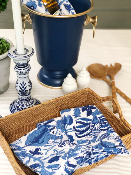 Blue and white candlesticks, dinner napkins, and ice bucket for a blue and white table setting.