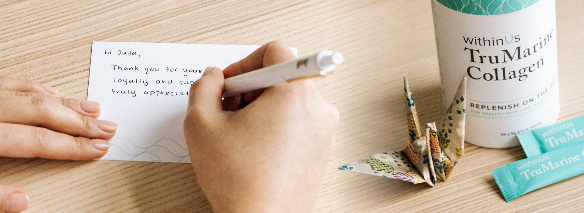 Our Philosophy - Woman writing a Thank you letter with WithinUs TruMarine Collagen and a paper crane beside her.