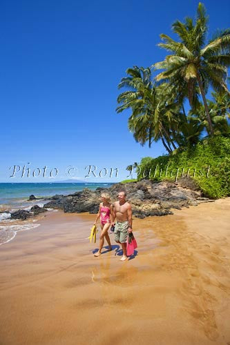 Couple about to go snorkeling at Changs Beach, Makena, Maui, Hawaii