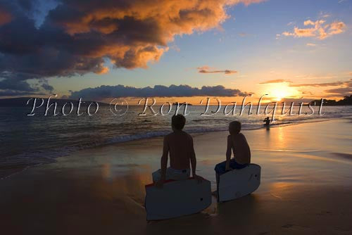 Teenage boogie boarders at sunset at Big Beach, Makena, Maui, Hawaii
