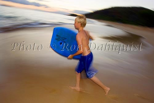 Teenager running to catch a wave as the sun goes down. Big Beach, Makena, Maui, Hawaii Picture