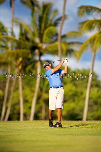 Man golfing in Hawaii with palm trees in background. Picture