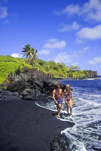 Honeymoon couple, walking on Black Sand Beach at Waianapanapa State Park, Hana, Maui, Hawaii
