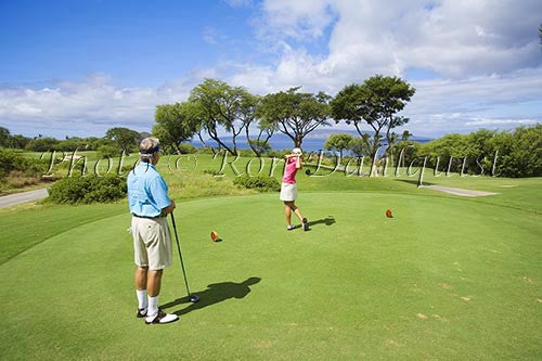 Couple playing golf at the Wailea Gold Golf Course, Wailea, Maui, Hawaii Picture Photo