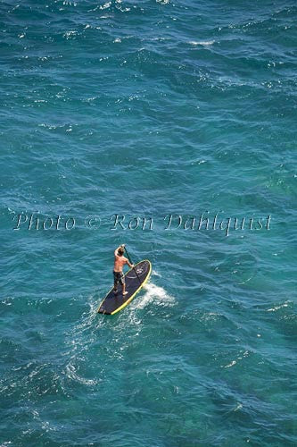Man stand-up paddle boarding over shallow reef on Lanai, Hawaii