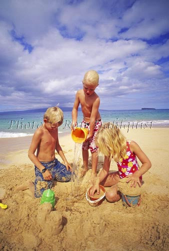 Three young children, playing in the sand at Big Beach, Maui, Hawaii