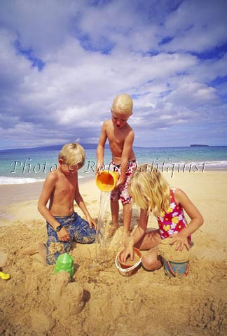 Three young children, playing in the sand at Big Beach, Maui, Hawaii - Hawaiipictures.com