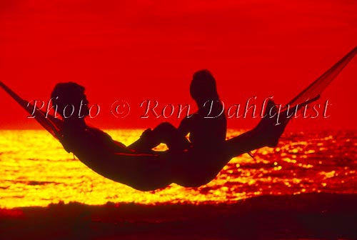 Silhouette of couple in hammock at sunset, Maui, Hawaii