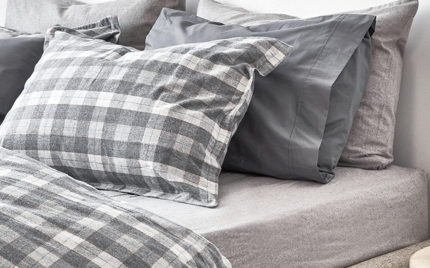Flannel bedding gray with plaid. Pillows sitting on a bed.