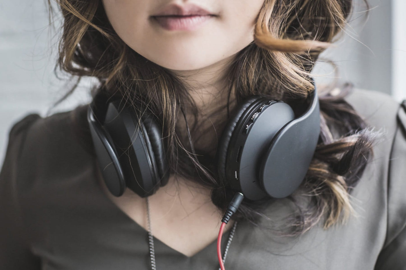 Young woman wearing headphones around her neck