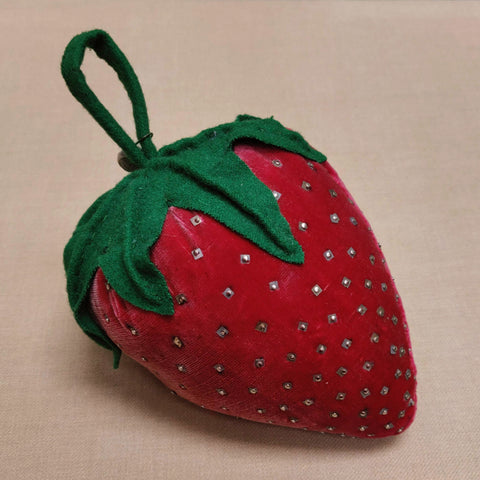 A large strawberry pin cushion
