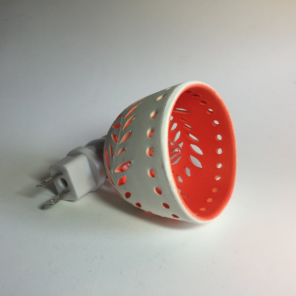 round night light in white with wavey leaf designs and yellow orange interior