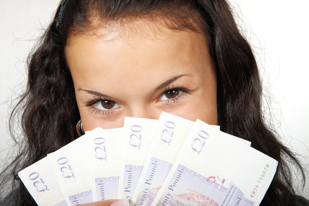 woman holding cash over face
