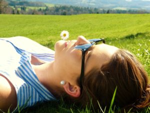 woman with flower in mouth lying down in field