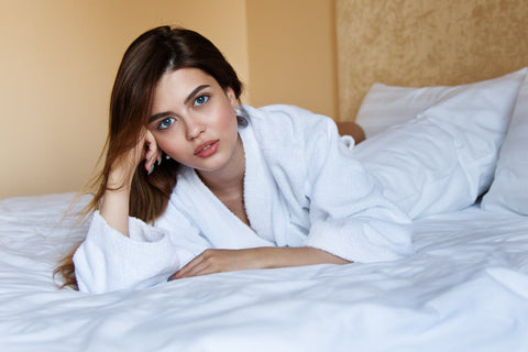 beautiful woman in robe lying on bed