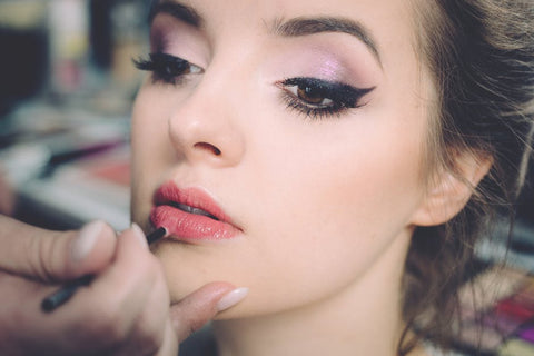 woman with makeup applying lip gloss