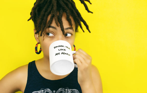 Image of a Black woman drinking from one of Ivy's Tea Co.'s Drink Tea Like An Adult mugs, no longer available.