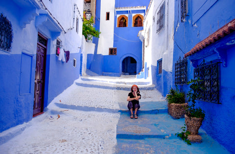 Nicole takes in the bold, blue colors of a quiet street in chefchaouen, Morocco