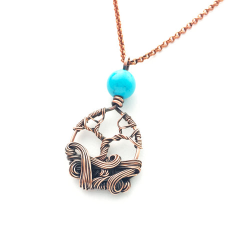 mini copper tree necklace with turquoise colored bead and decorative swirls.