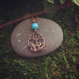 Mini swirling tree necklace with turquoise colored accent