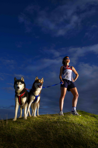 woman runner with her huskies
