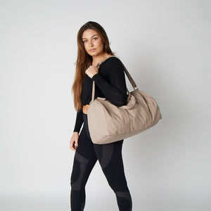 Beige color gym bag being held by a model on her shoulder